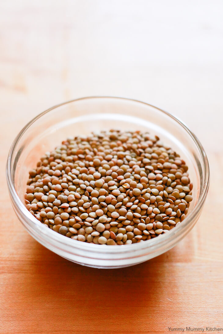 A bowl of dried green lentils is prepared for vegan lentil soup.
