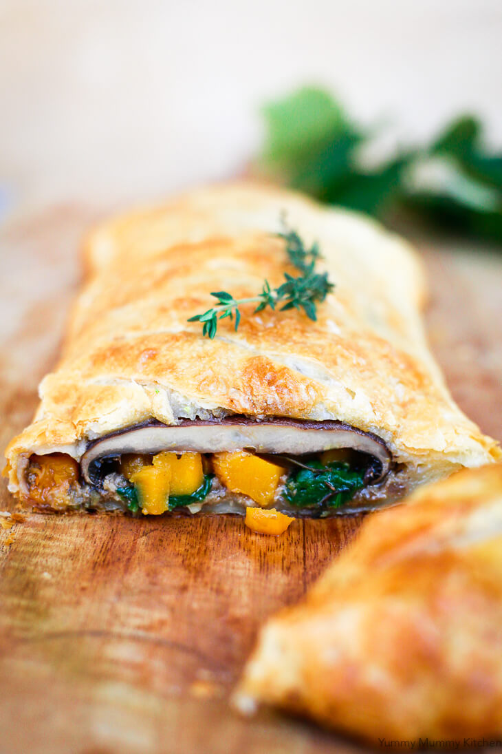 A slice of vegetarian vegan Wellington made with portobello mushroom, butternut squash, and spinach wrapped in puff pastry.