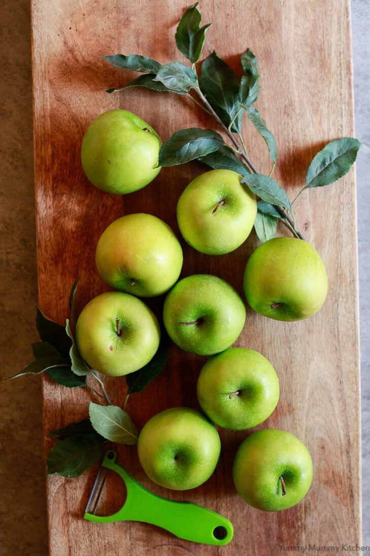 Green Granny Smith apples on a cutting board ready to get peeled for apple crumble pie.