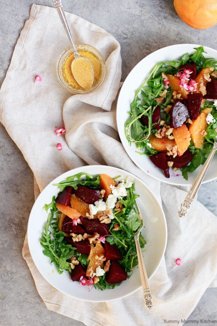 Bowls of beautiful beet salad with arugula, goat cheese, walnuts, oranges, and a homemade beet salad dressing.