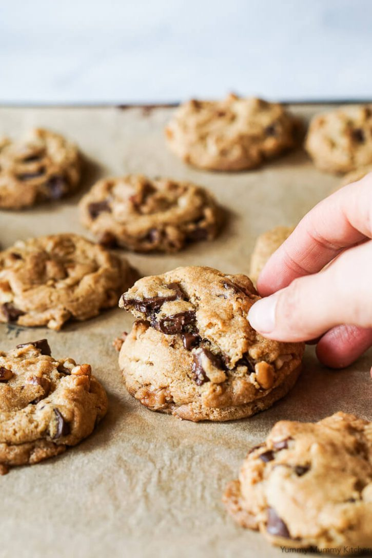 A hand reaches for half a soft and chewy vegan chocolate chip cookie with melty chocolate and walnuts. These look like the best vegan chocolate chip cookies ever.