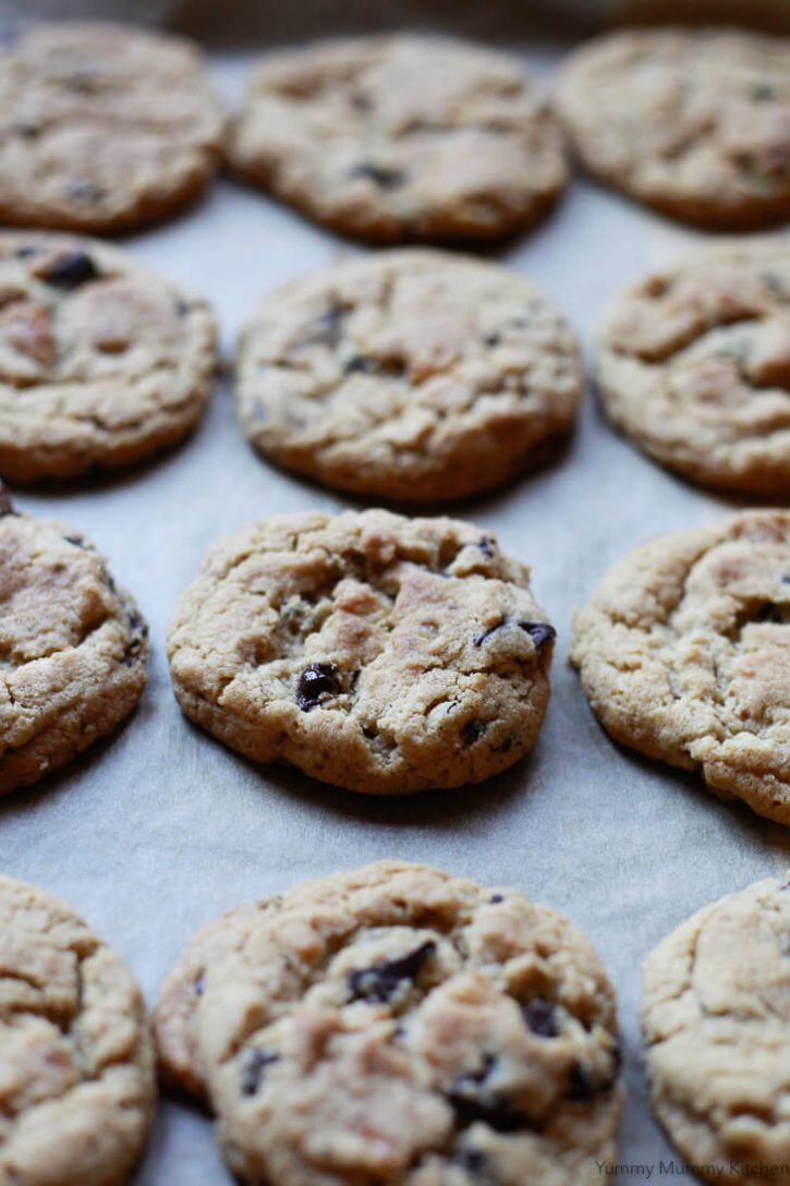 A cookie sheet of gluten free vegan chocolate chip cookies.
