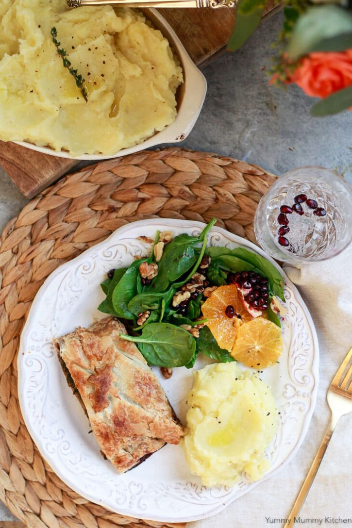 A beautiful vegan holiday (Thanksgiving or Christmas) dinner menu with vegan olive oil truffle mashed potatoes, vegetarian Wellington, and spinach salad with oranges and pomegranate.