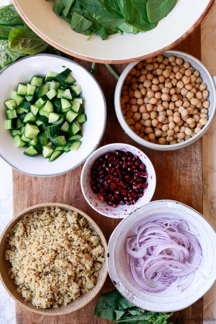 Ingredients for chickpea quinoa salad on a cutting board: cooked quinoa, spinach, chickpeas, chopped cucumber, pomegranate, and red onion.