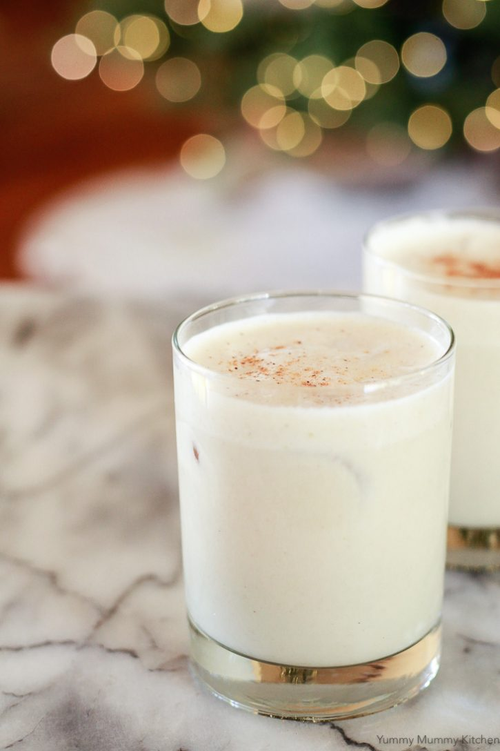 Glasses of vegan eggnog in front of bokeh Christmas tree lights. This creamy cold vegan nutmeg is made with almond and coconut milk, sweetened with dates, and topped with nutmeg.