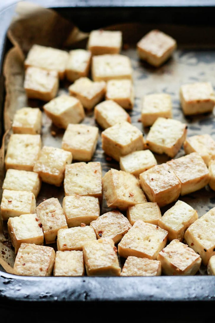 Golden brown crispy baked tofu cubes on a baking sheet just out of the oven.