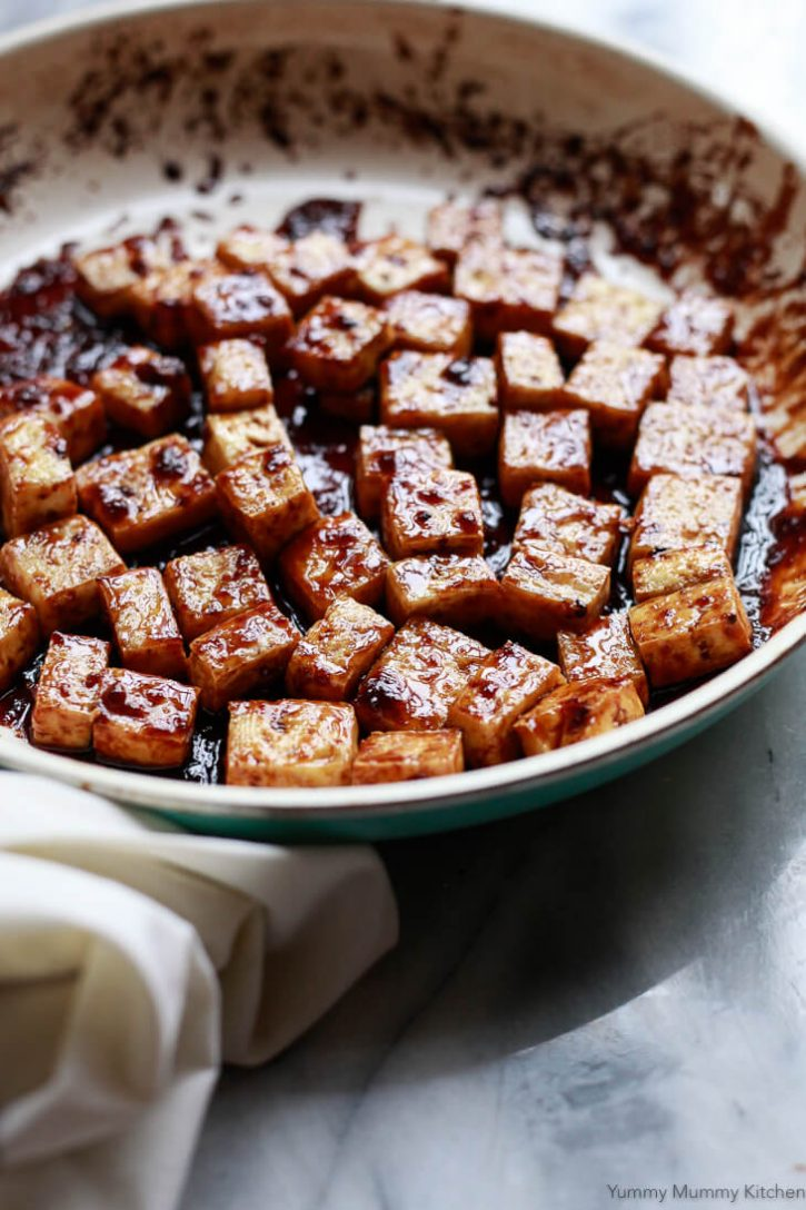 A frying pan filled with baked tofu coated in a sticky sweet and savory soy sauce ginger glaze.