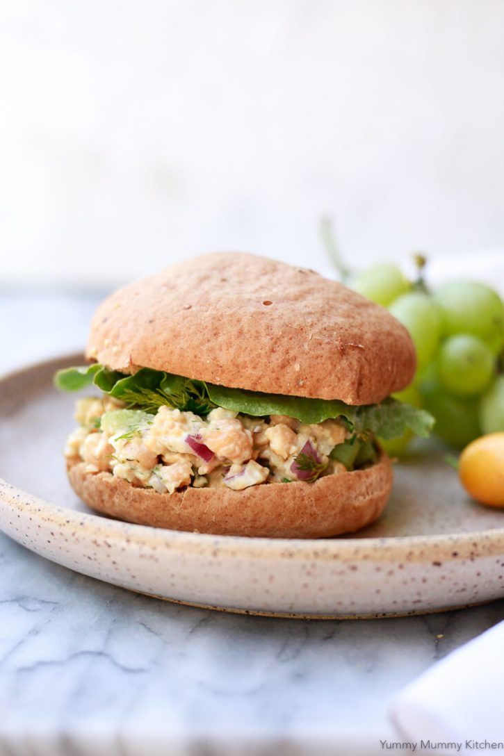 A whole smashed chickpea salad sandwich on a gluten-free bun with lettuce and fresh herbs on a plate for a healthy vegan gluten free lunch sandwich.