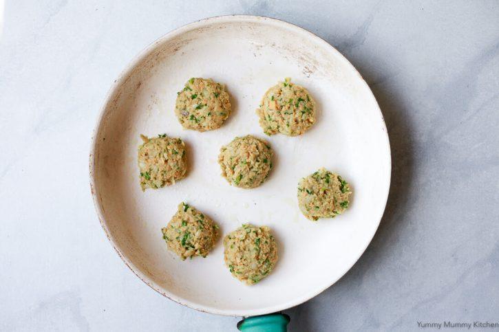 Uncooked falafel balls on a GreenPan ceramic frying pan.