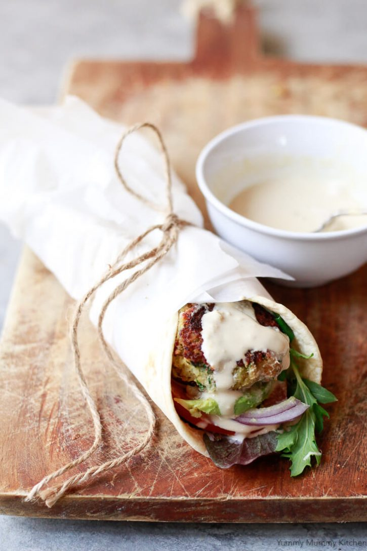 A homemade falafel wrap with lettuce, onions, tomato, and tahini sauce on a wooden cutting board.