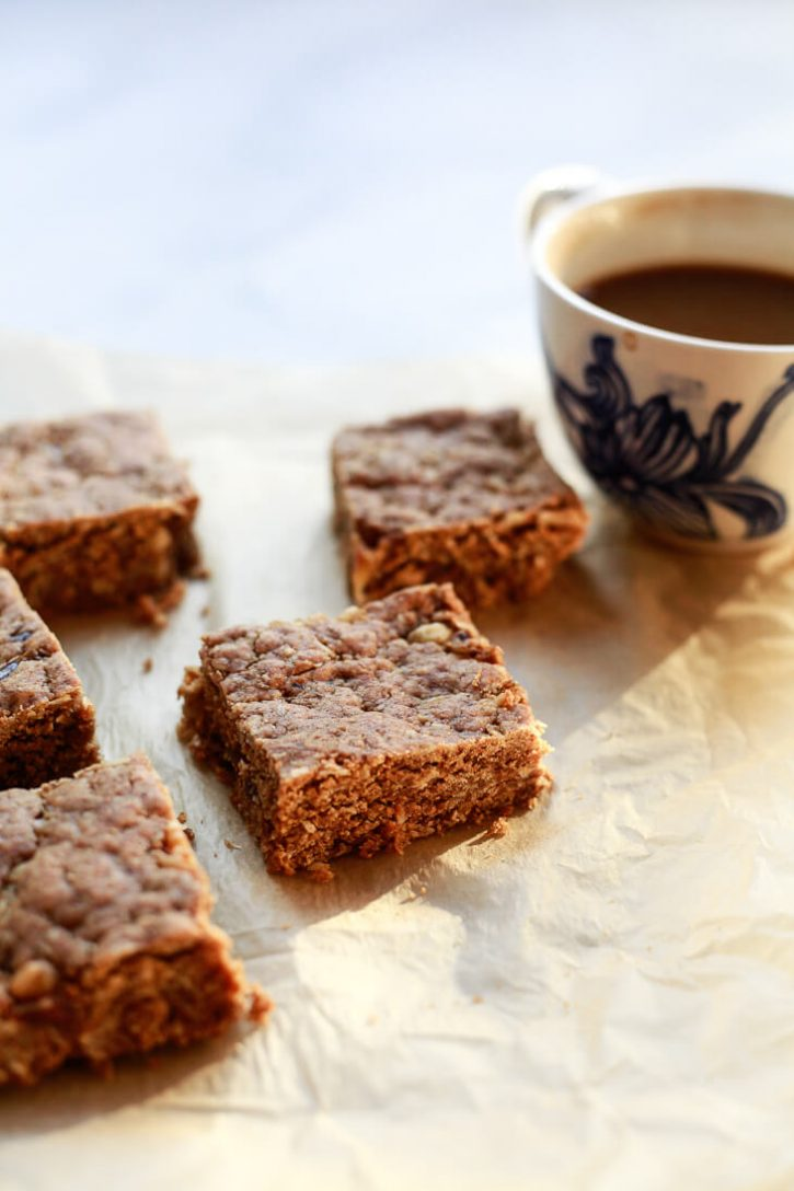 Peanut butter oatmeal snack bars on a piece of parchment paper with a cup of coffee in the background.