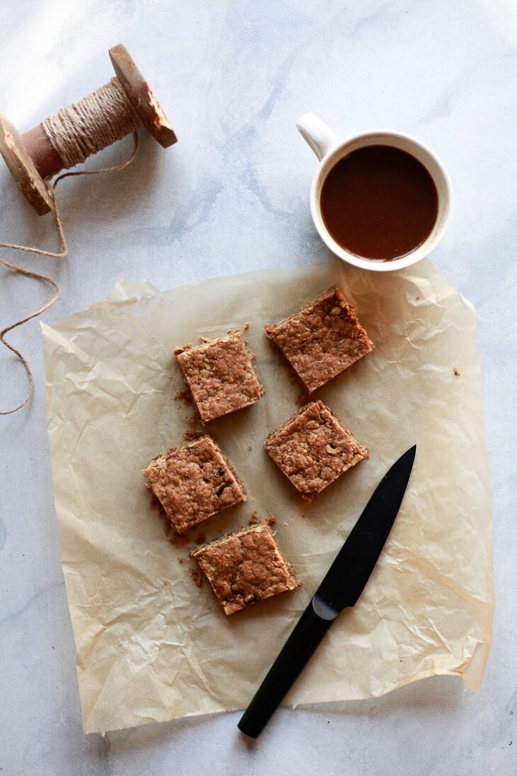 Peanut butter oatmeal snack squares are cut on a piece of parchment paper. These delicious bars taste like a combination of granola bars, blondies, and snack cake. This is a great portable high protein vegan snack.