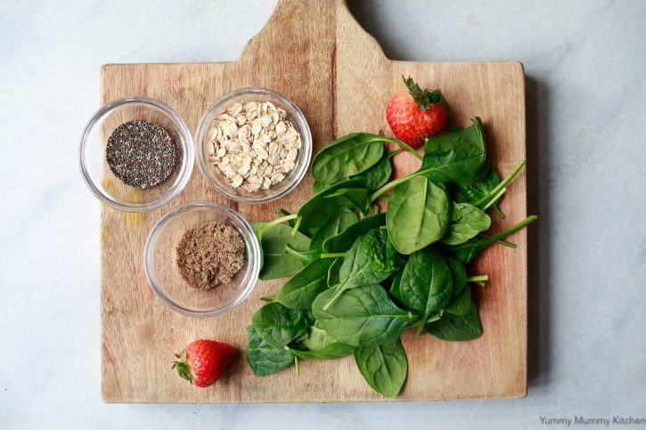 Small bowls of chia seeds, flax meal, oats, and baby spinach on a cutting board.