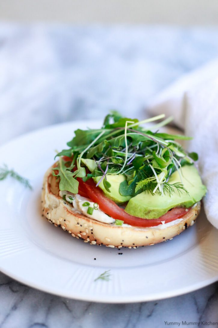 Half an everything bagel topped with homemade vegan cream cheese, tomato, avocado, and micro greens. A beautiful plant-based breakfast idea.