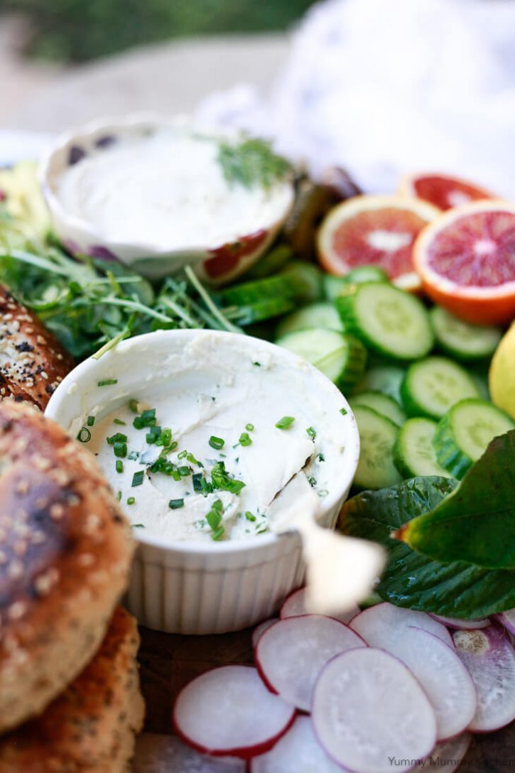 A small bowl of homemade dairy free vegan cream cheese topped with chives sits on a beautiful brunch bagel platter.