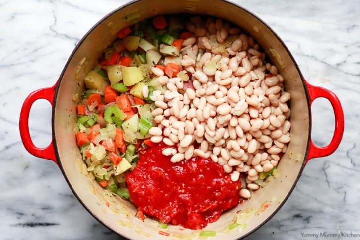 Cannellini beans and tomatoes are added to sauteed vegetables in a red Dutch oven while making white bean and kale soup.