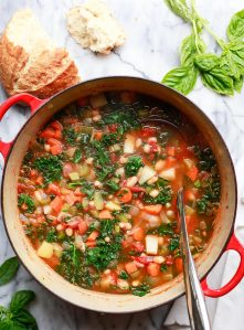 Healthy winter white bean and kale vegetable soup recipe in a red Le Creuset Dutch oven.