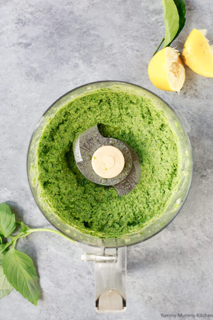 Beautiful bright green vegan pea pesto in a food processor.