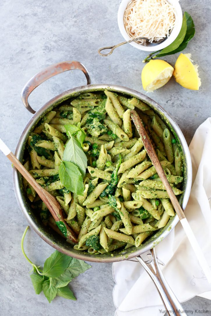 A pot filled with bright green vegan pea pesto penne pasta topped with fresh basil leaves.