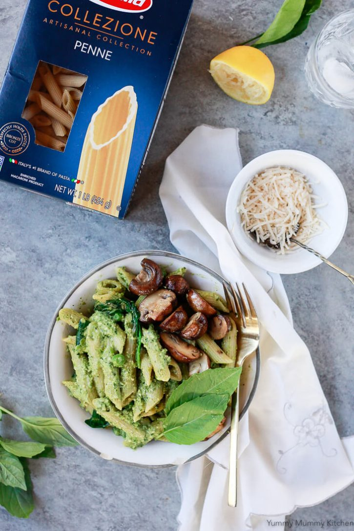 A bowl of vegan pea pesto pasta with mushrooms and spinach sit on a grey countertop with a bowl of vegan cheese.
