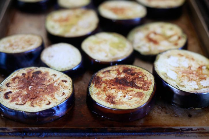 Browned eggplant slices on a griddle are the start of baked eggplant parmesan.
