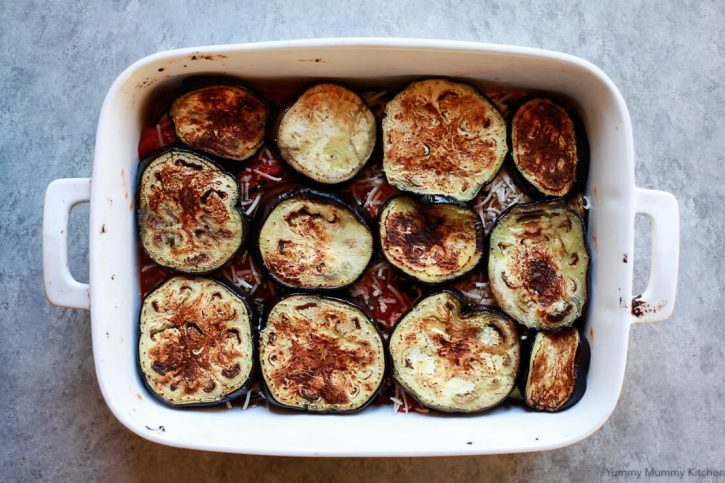 The top layer of eggplant is assembled on top of tomato sauce and vegan parmesan for a healthy vegan eggplant parmesan recipe.