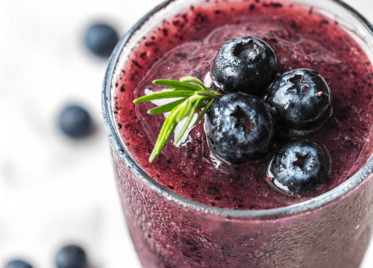 Beautiful purple blueberry green smoothie in a glass.