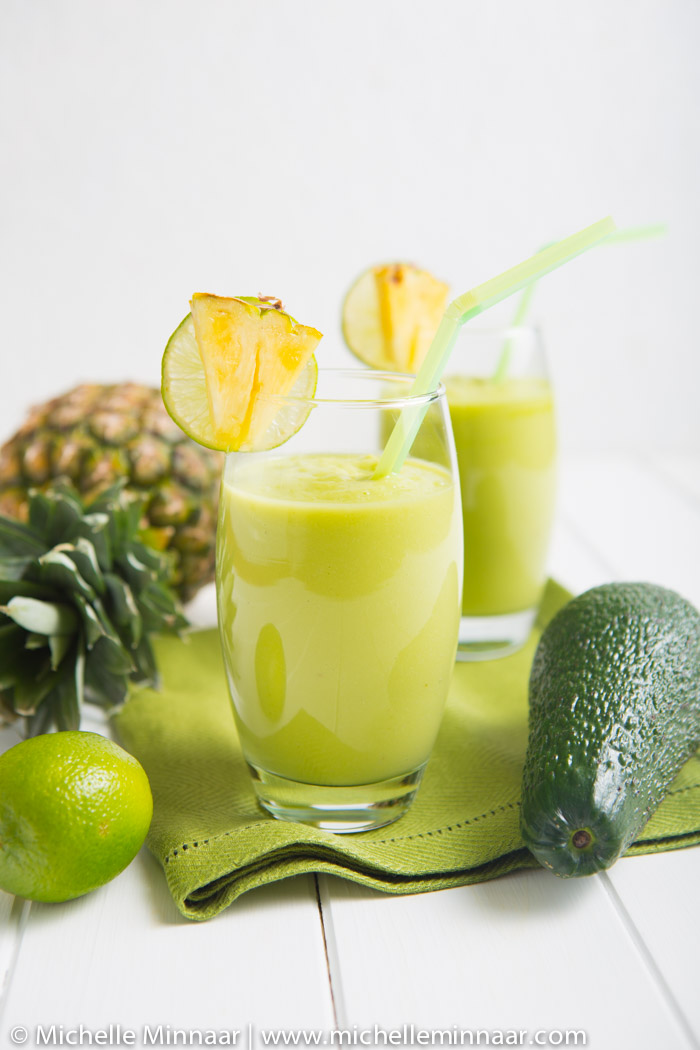 Two glasses filled with a pineapple avocado green smoothie and garnished with pineapple wedges.