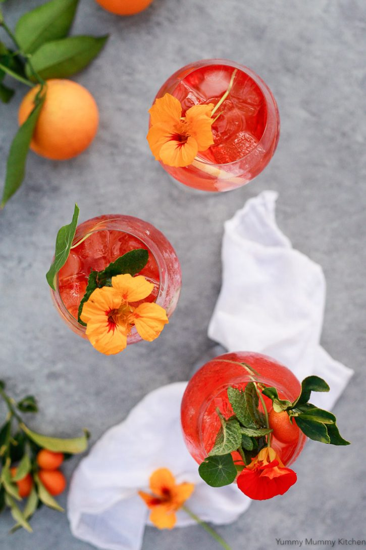 3 Italian Aperol Spritz cocktails on an outdoor table. This Aperol Spritz recipe is topped with nasturtiums.