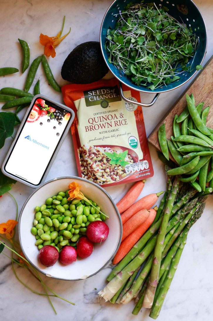 Ingredients for Quinoa and Brown rice grain bowls with vegetables sit on a marble countertop.