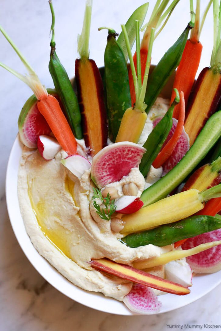 Homemade hummus in a white bowl topped with beautiful raw carrots, cucumbers, snap peas, and radish for dipping.