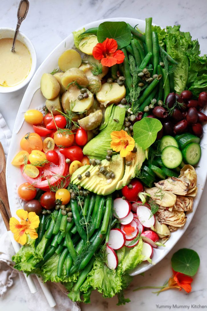 A beautiful white oval platter filled with a vegan Nicoise salad made with green beans, tomatoes, radish, artichoke hearts, avocado, tomatoes, potatoes, edible flowers, and dill. A small bowl of creamy shallot vinaigrette dressing on the side.