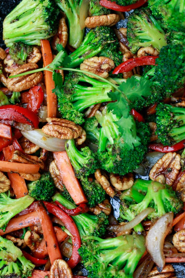 Stir fry vegetables with broccoli, carrots, bell pepper, onions, and pecans.