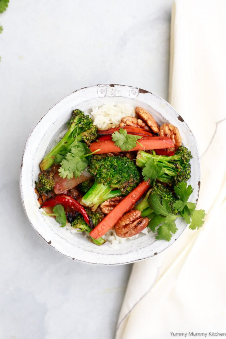 A white ceramic bowl filled with white rice and stir fry vegetables like broccoli and carrots.