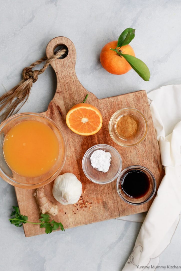 The ingredients for orange stir fry sauce sit on a wooden cutting board on a white countertop.