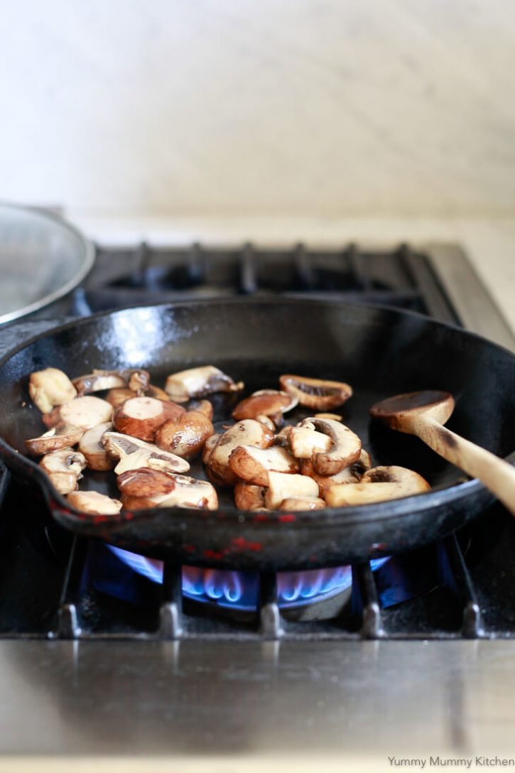 Sliced mushrooms saute in a cast iron skillet on the stove.