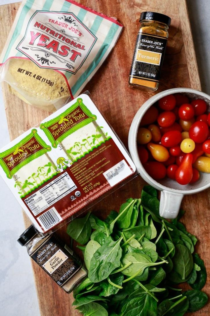 Ingredients for tofu scramble on a cutting board: Trader Joe's organic tofu, cherry tomatoes, nutritional yeast, turmeric, and spinach.