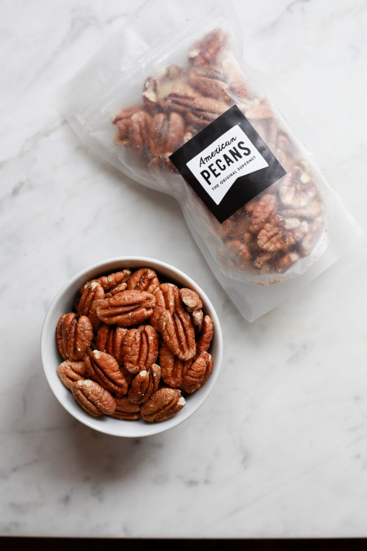 A bag of American Pecans with a bowl of pecan halves on a white marble countertop.