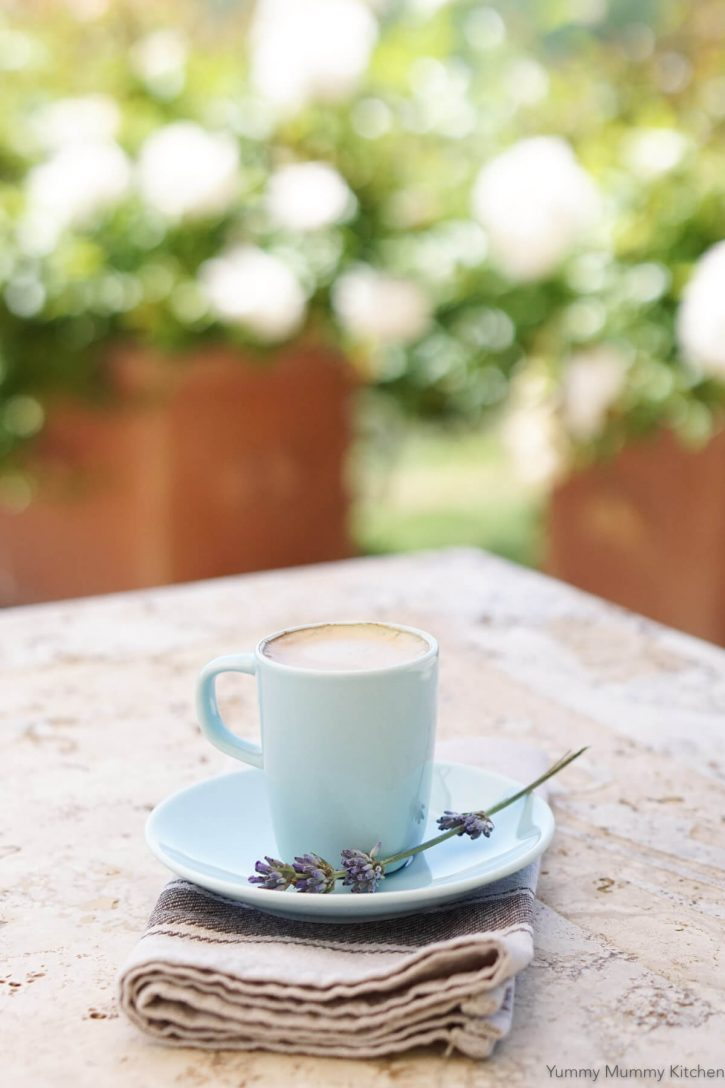 A small blue espresso cup and saucer with an espresso shot sit on an outdoor table in Tuscany, Italy.