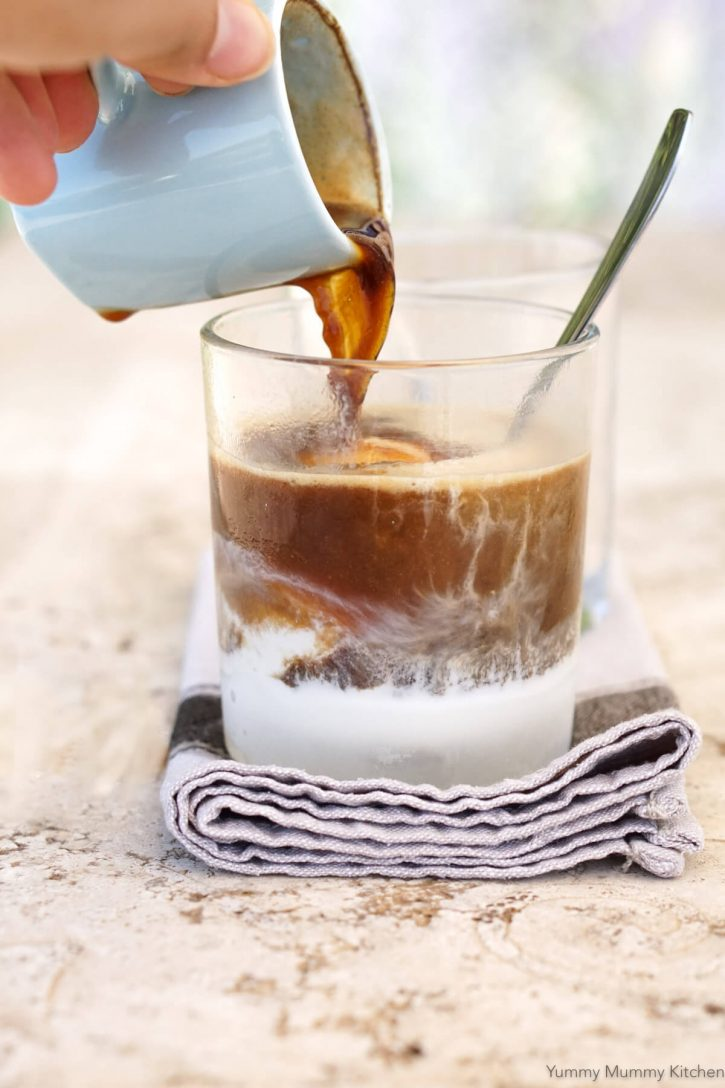 A hand pours a shot of espresso coffee over a scoop of ice cream to make affogato.