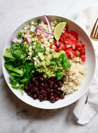 A vegetarian Chipotle inspired burrito bowl with brown rice, black beans, salsa, corn salsa, romaine, and guacamole.