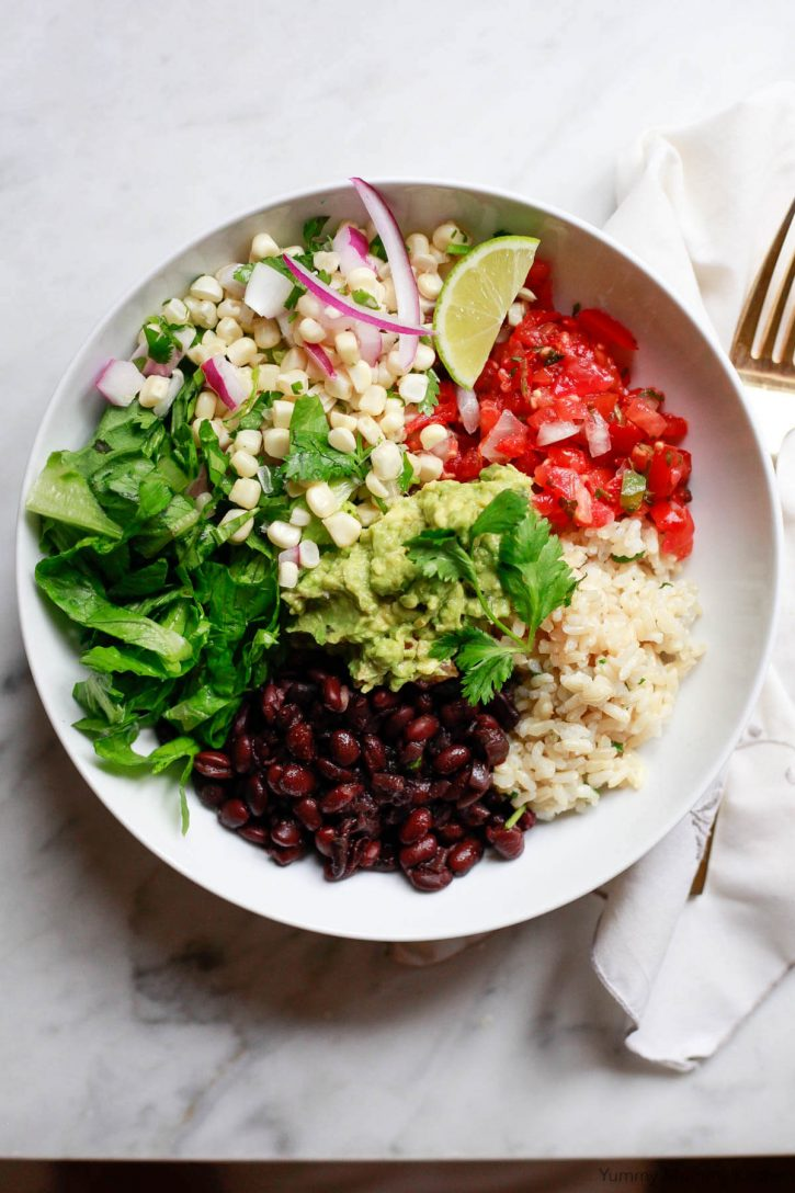 A white bowl filled with black beans, cilantro lime brown rice, corn salsa, tomato salsa, romaine lettuce, and guacamole sits on a white marble countertop.
