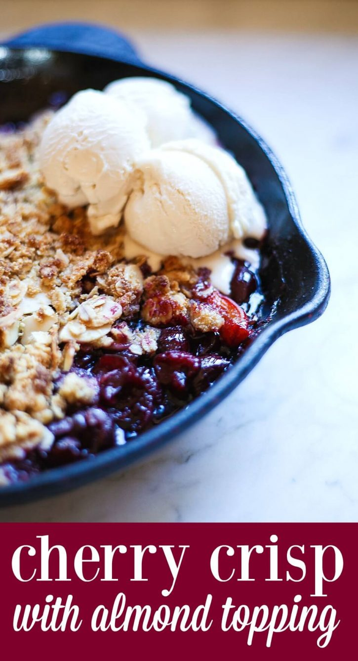 A close-up of a cherry crisp made with fresh cherries and a gluten free almond oat crumble topping. This cherry crisp is made in a skillet and topped with scoops of vanilla ice cream.