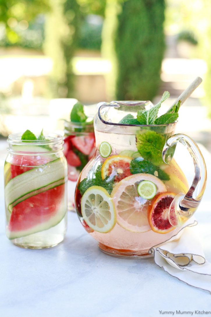 Three detox water recipes in glass pitchers sit on an outdoor table. A glass pitcher with citrus infused detox water, a jar with cucumber and watermelon, and another jar with strawberries and mint.