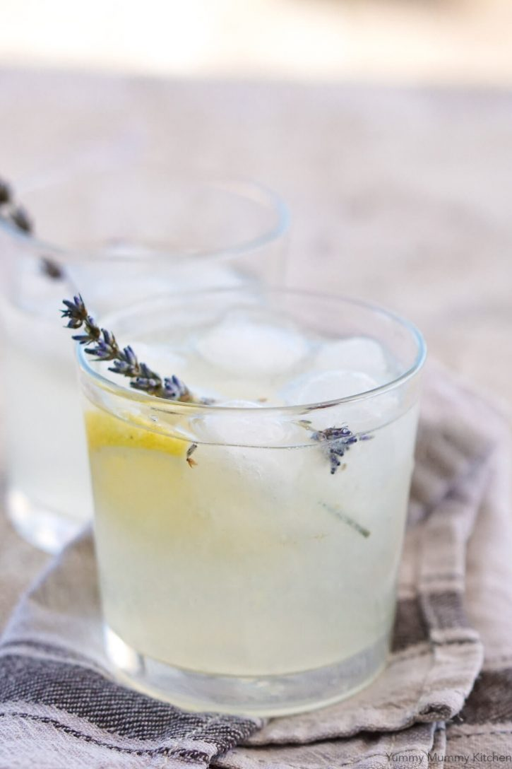 A glass of cold lavender lemonade with ice and fresh lavender.