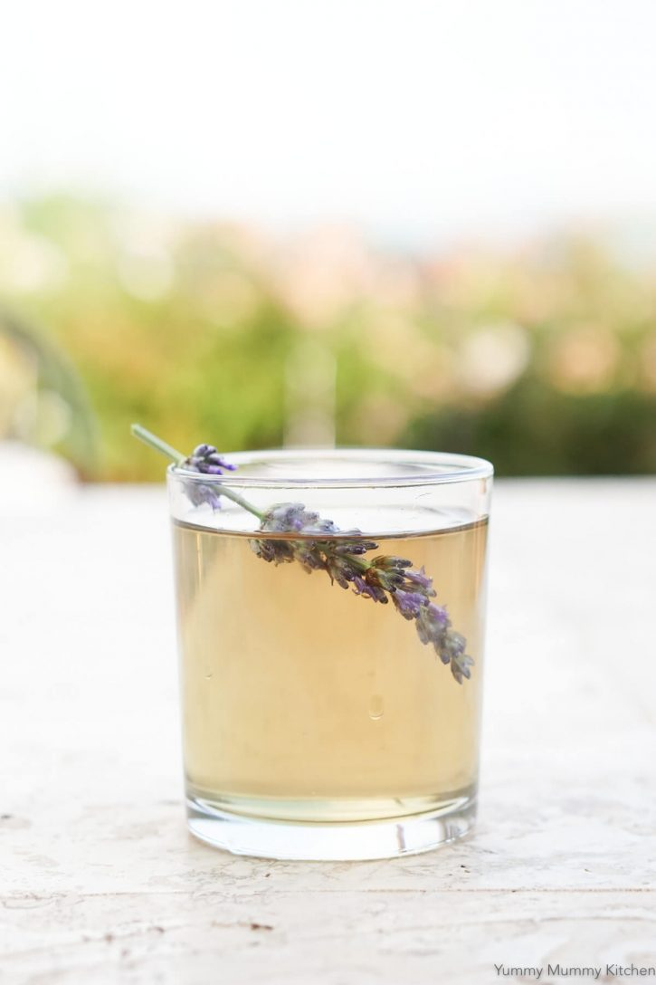 A glass filled with lavender simple and a lavender stem sits on an outdoor table.