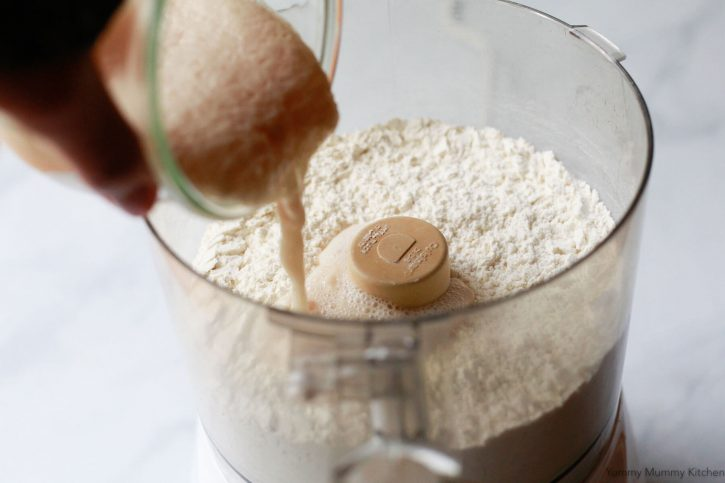 Proofed yeast and water is poured into flour in a food processor.