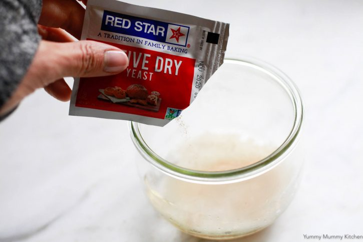 A packet of Red Star active dry yeast pouring into a bowl of water.