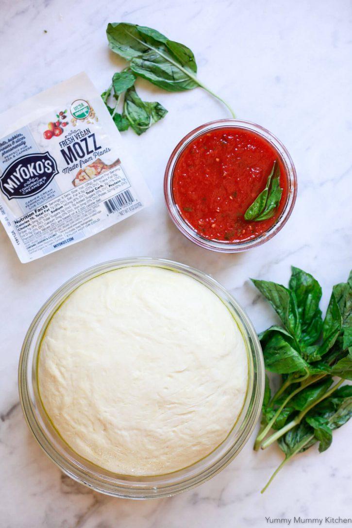 Homemade pizza dough, sauce, and Miyoko's Mozz vegan Mozzarella on a marble countertop.
