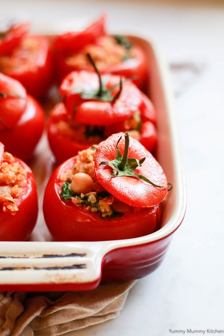 A close-up of baked stuffed tomatoes with quinoa, spinach, and chickpeas in a red casserole dish on a white countertop.
